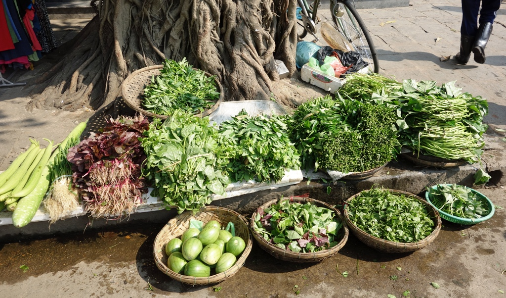 Baskets full of greens at the Hoi An market