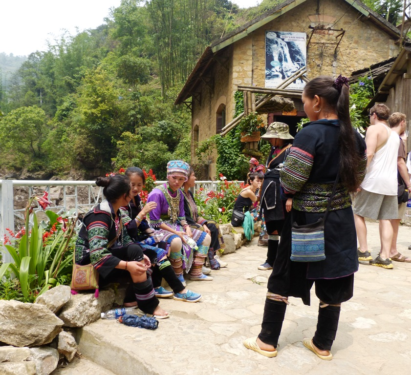 H'mong girls in two of their traditional outfits. The one sitiing down in the middle is our guide, Ha